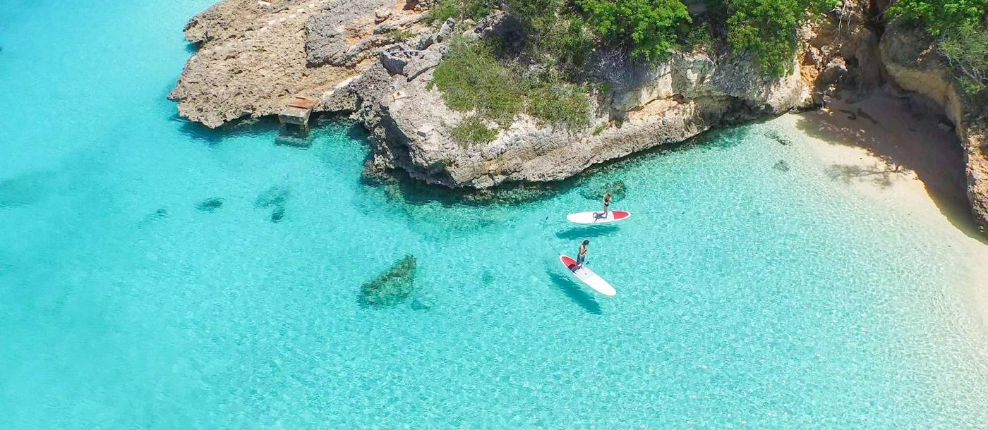 aerial shot of a couple paddle boarding near Malliouhana, Anguilla