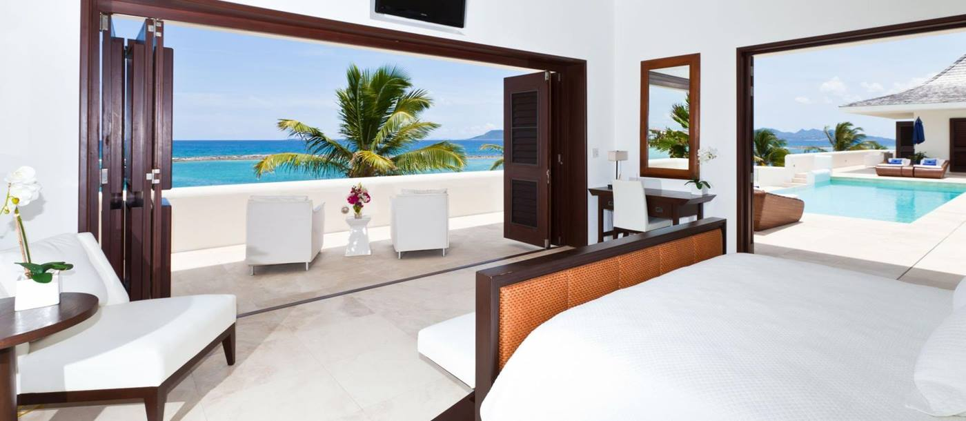 double bedroom with swimming pool and terrace access at le bleu, anguilla