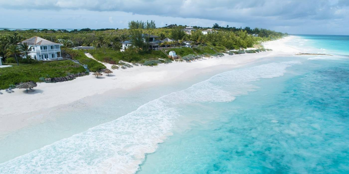 Aerial view of villa and beach with white sand and crystal blue water at Sea Siren in the Bahamas, Caribbean
