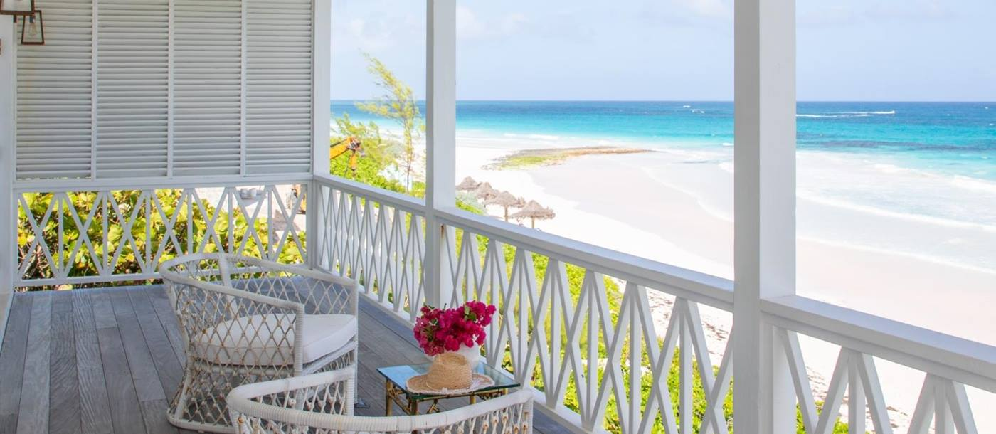 Balcony with comfy chairs, coffee table, flowers and sea view at Sea Siren in the Bahamas, Caribbean