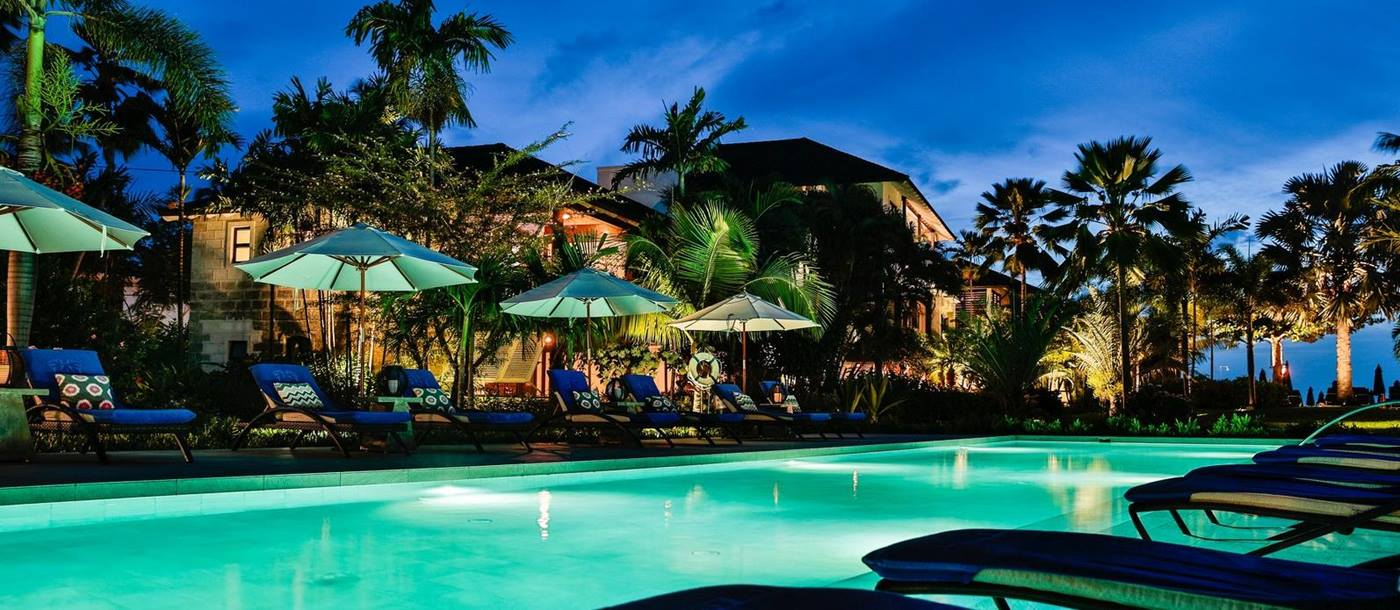 Swimming pool and sunloungers at night of the Sandpiper, Barbados