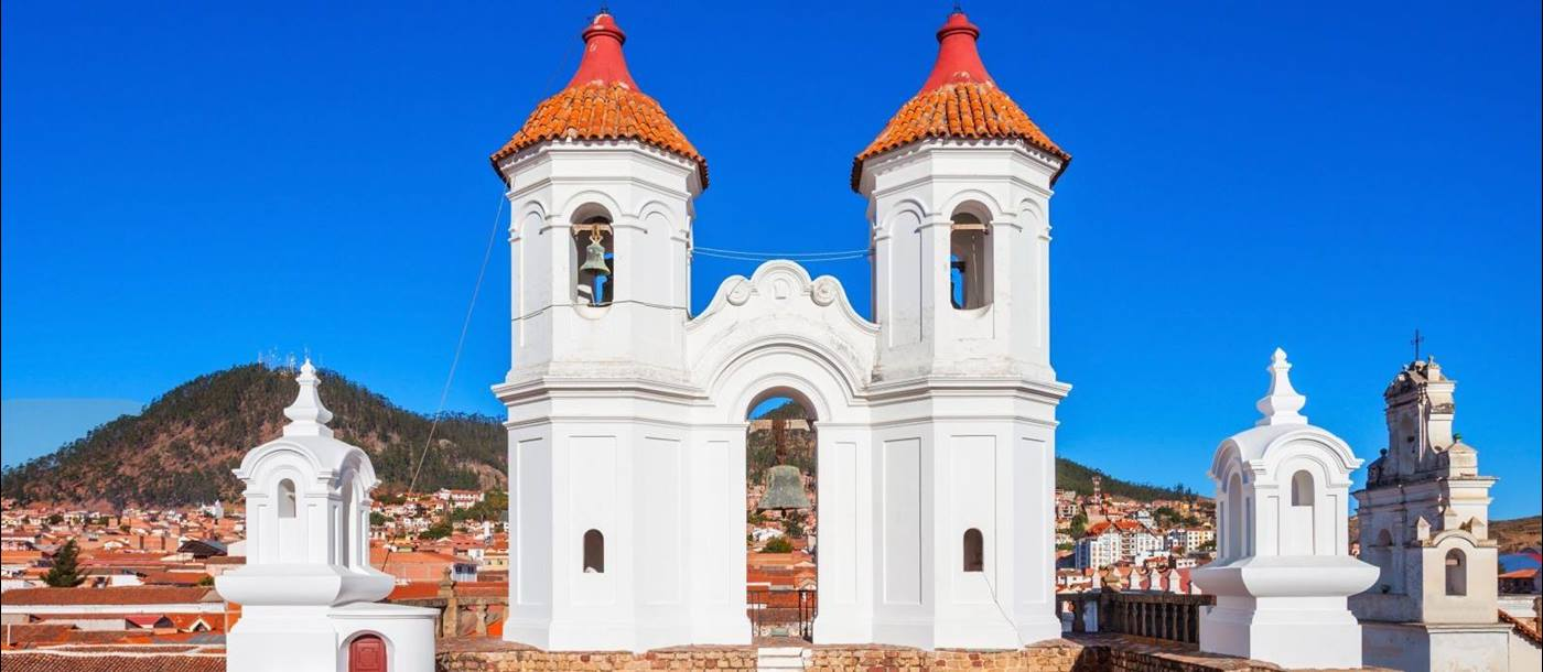 Whitewashed towers set against a bright blue sky in the city of Sucre in Bolivia