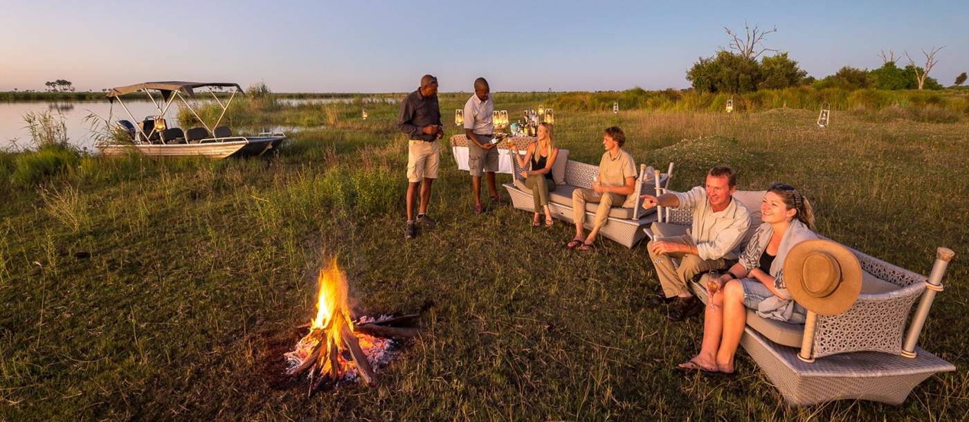 Guests enjoying sundowners with a campfire on the banks of the Okavango