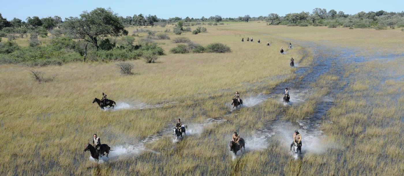 Aerial shot of group of people riding through the waters of the Okavango