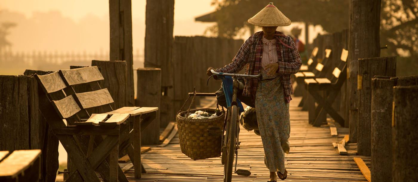 biker walking over an u bein bridge in Myanmar