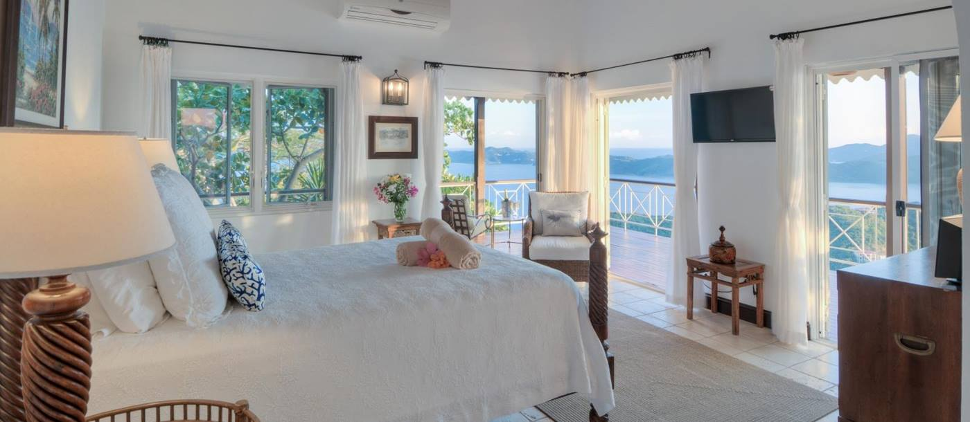 Double bedroom with access to a balcony and extensive windows overlooking the neighbouring islands in the British Virgin Islands at luxury villa St Bernard's Hill House