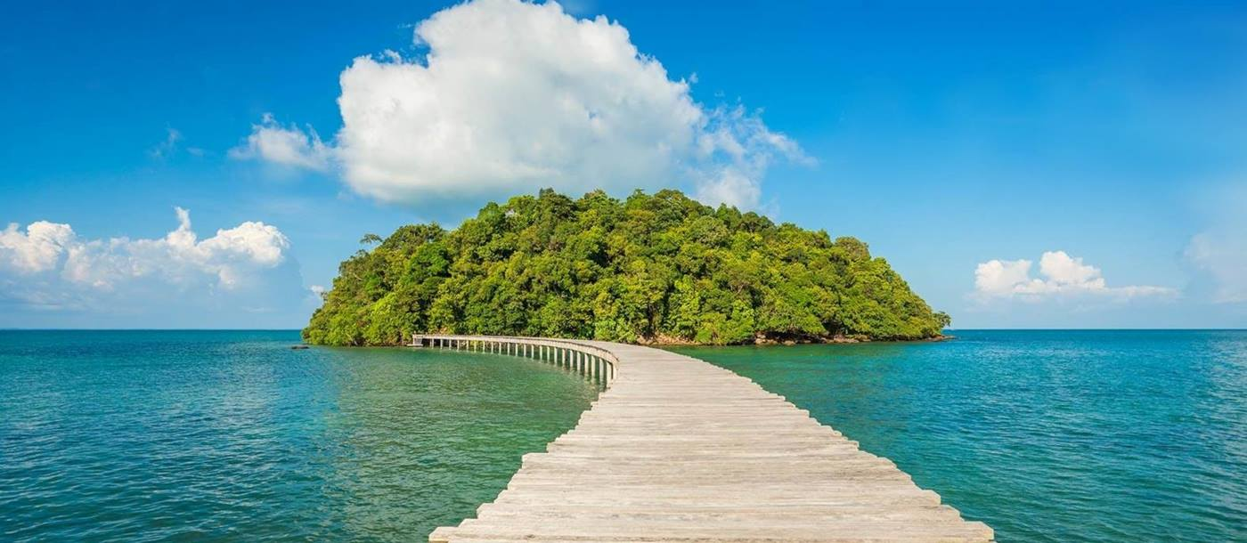 Wooden jetty leads to lush green island