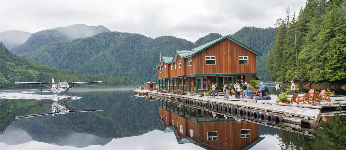 Seaplane Lodge with mountains in background reflecting in water, Great Bear Lodge, Canada