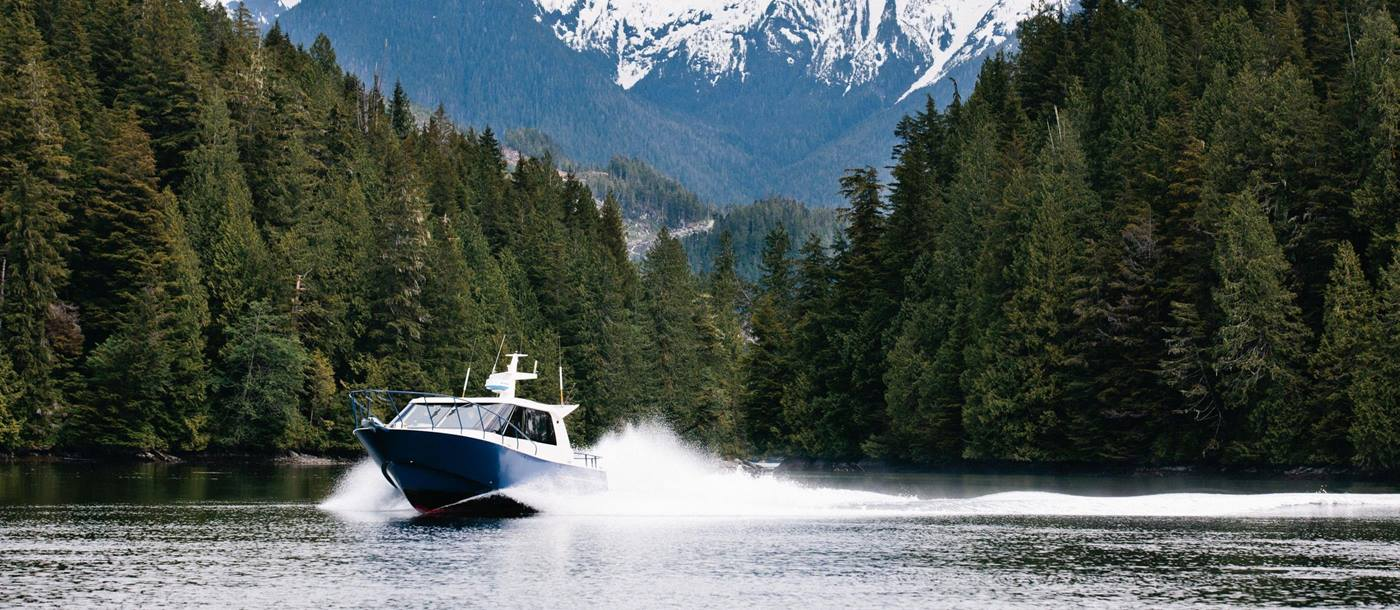 Speedboat with mountains and forest near Nimmo Bay Wilderness Resort, Canada