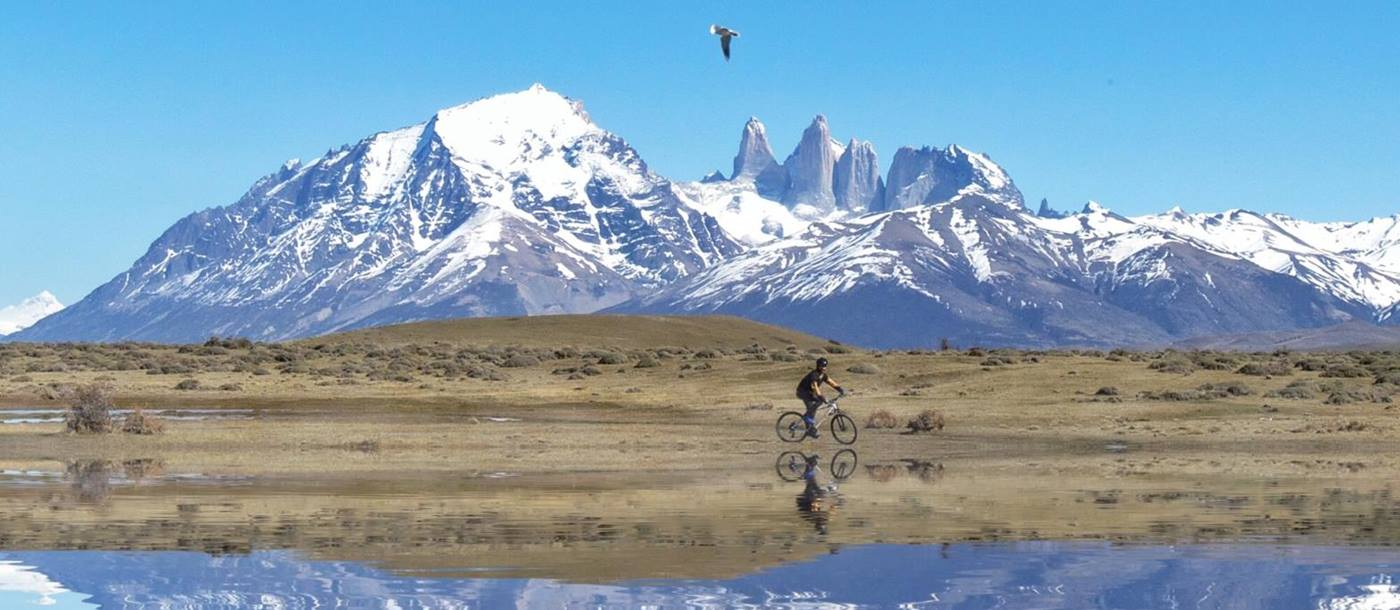 Mirror-like reflection of a cyclist withsnowy mountains in the background