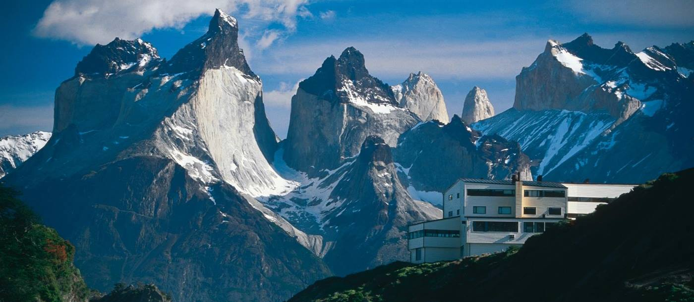 Exterior of Explora Patagonia with impressive mountain range and waterfall