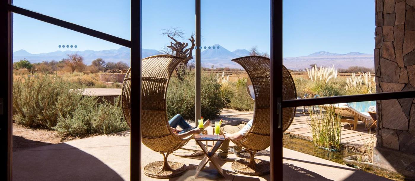 Two big chairs on a terrace overlooking the landscape and mountains