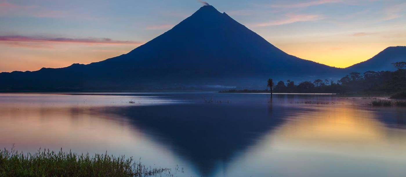 Reflection of the Arenal Volcano on Lake Arenal at sunrise