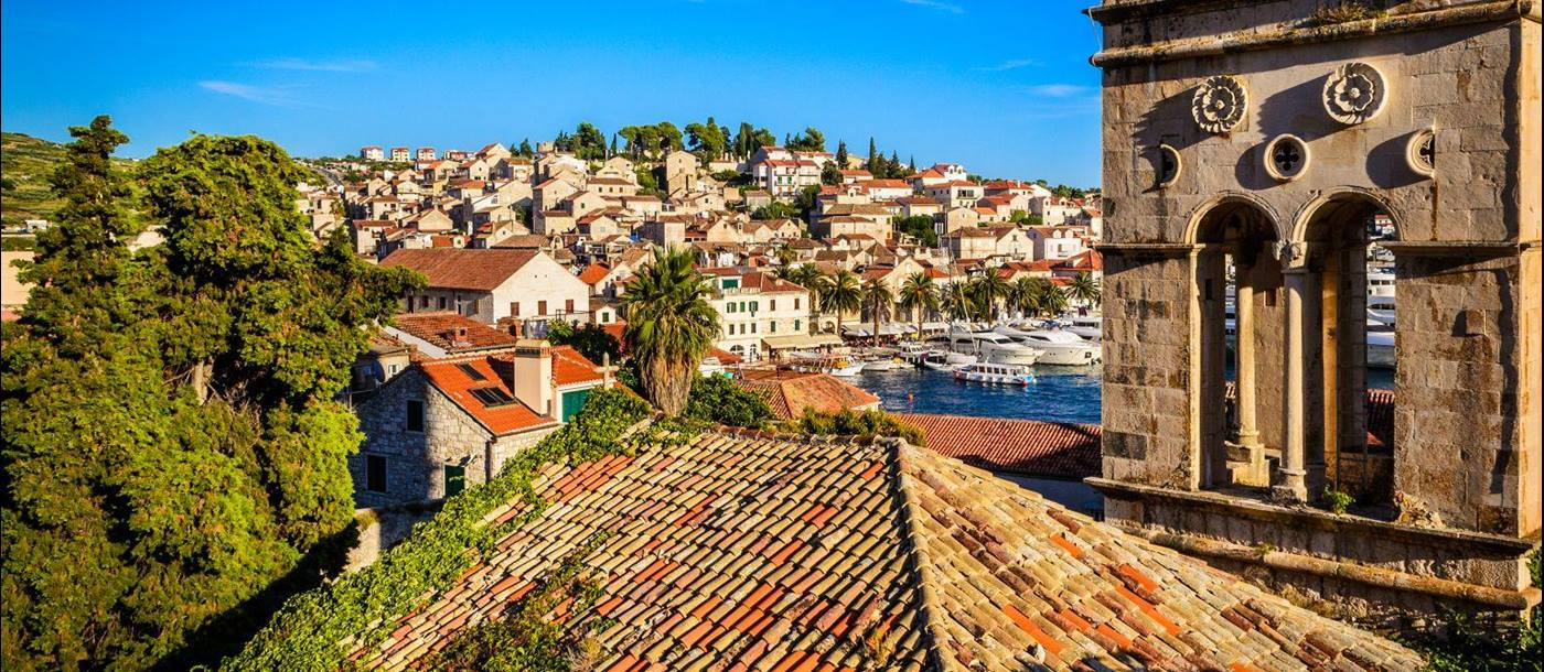 Historic church covered in ivy and the rooftops of Hvar old town in Croatia