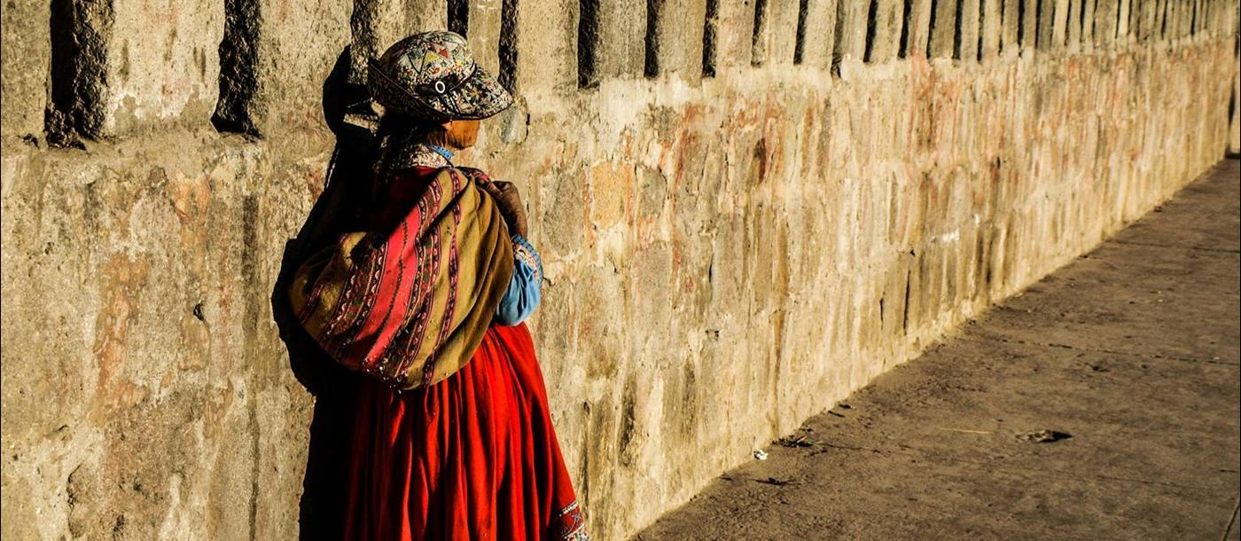 Traditional dress worn by a child on a wall, Ecuador