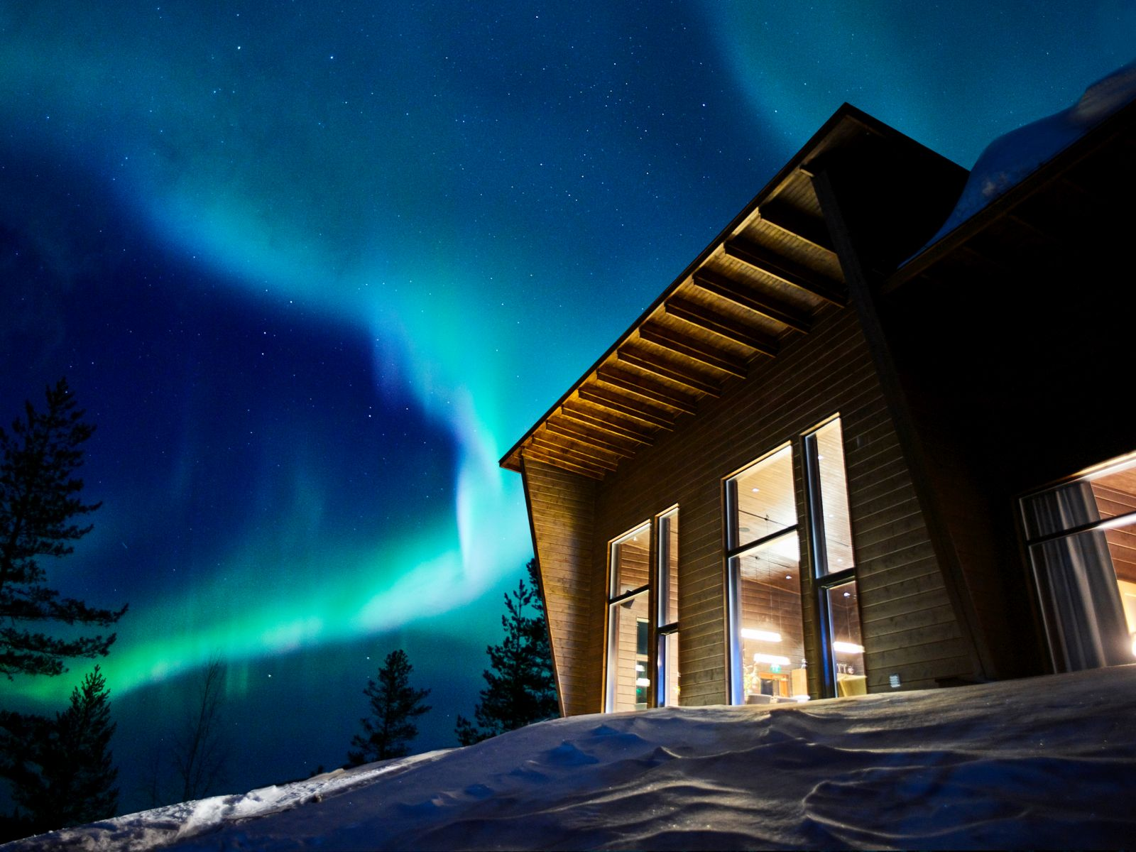 The Northern Lights shining over Octola wilderness lodge in Finland