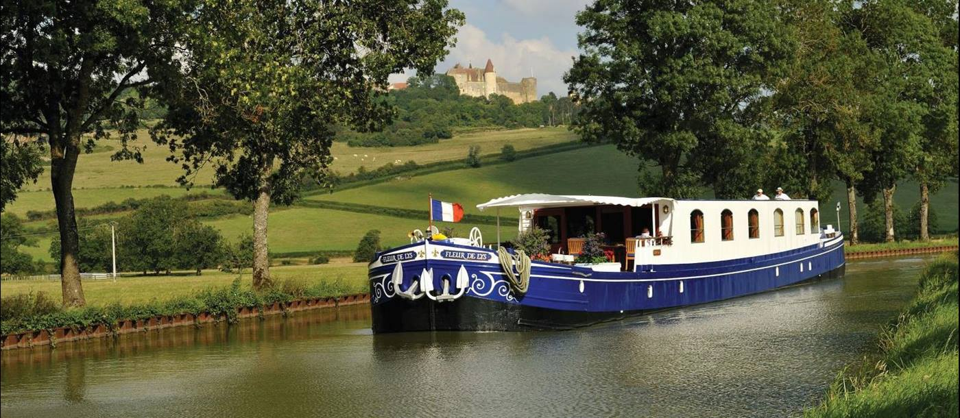 The Belmond Fleur de Lys river barge sailing through the French countryside