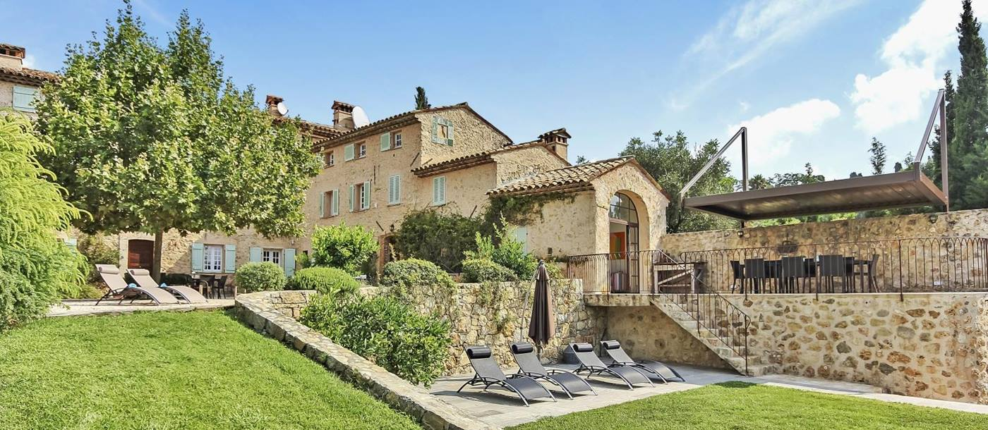 Garden with green grass, sun loungers and view of villa at La Bastide du Ciel on the Cote d'Azur, France
