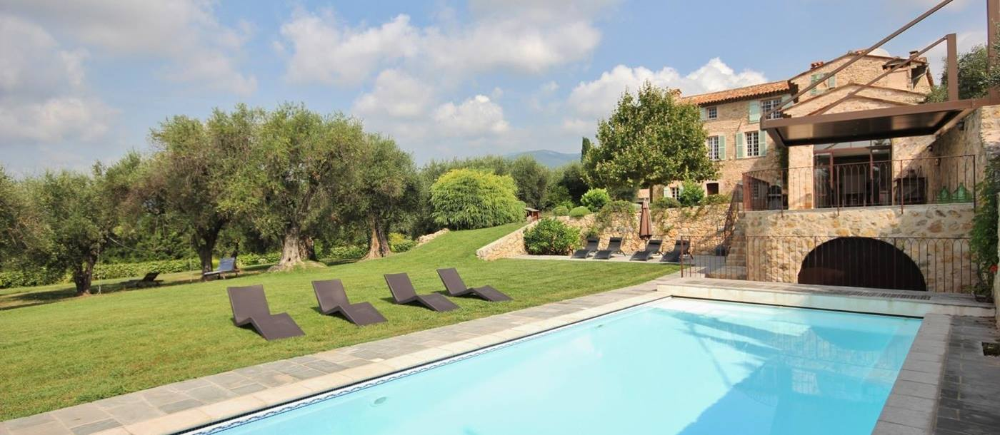 Pool and garden with sun loungers, olive trees and view of villa at La Bastide du Ciel on the Cote d'Azur, France