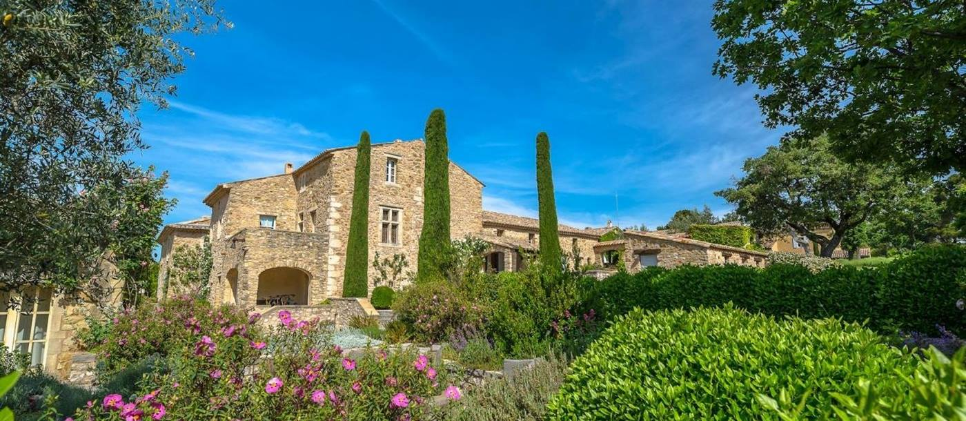 Façade and gardens with plants, flowers and trees at Domaine des Coteaux in Provence, France