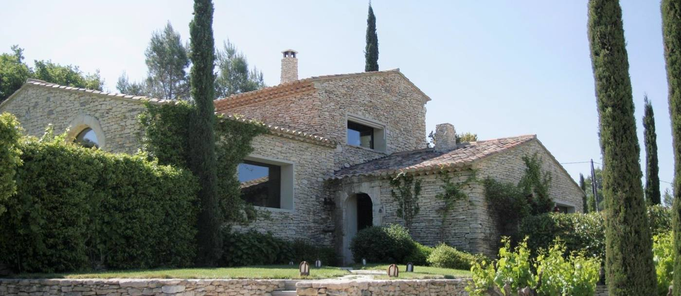 Façade and garden with vines and trees at Le Clos in Provence, France