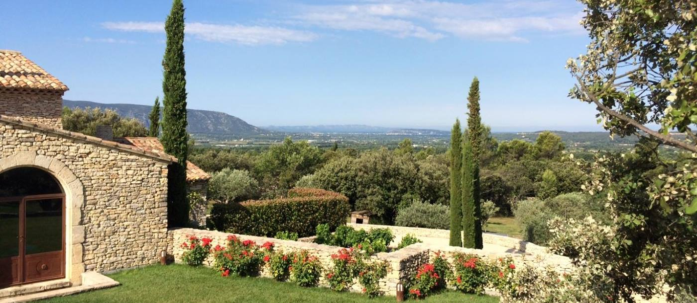 Garden with flowers, trees and countryside view at Le Clos in Provence, France