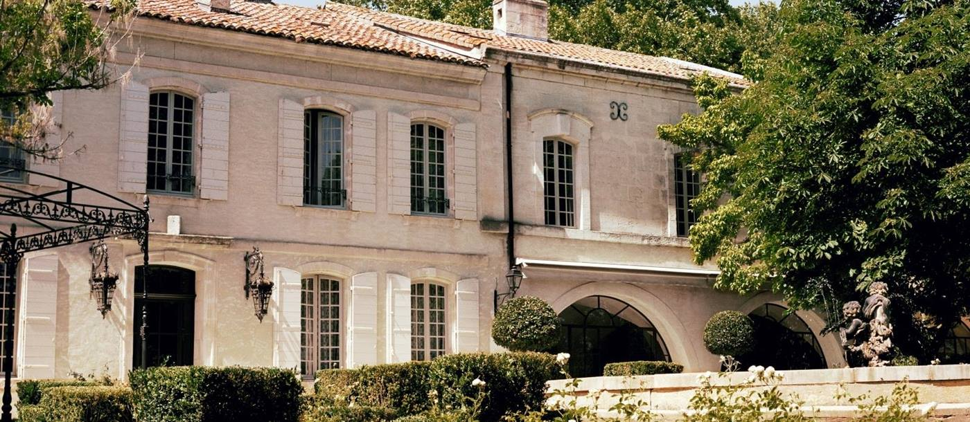 Pale stone exterior with white window shutters of Le Mas de Liliana, a luxury villa in Provence