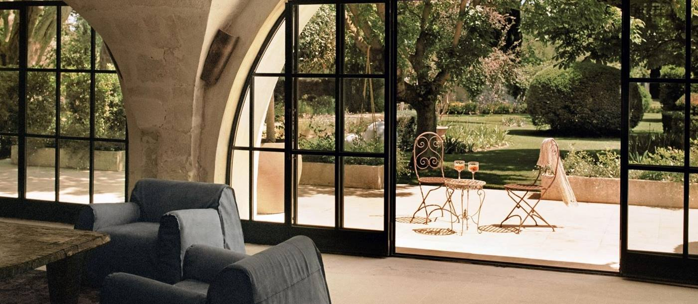 Large sliding glass doors that open from the sitting area onto the terrace with two chairs and a round table and views of the garden