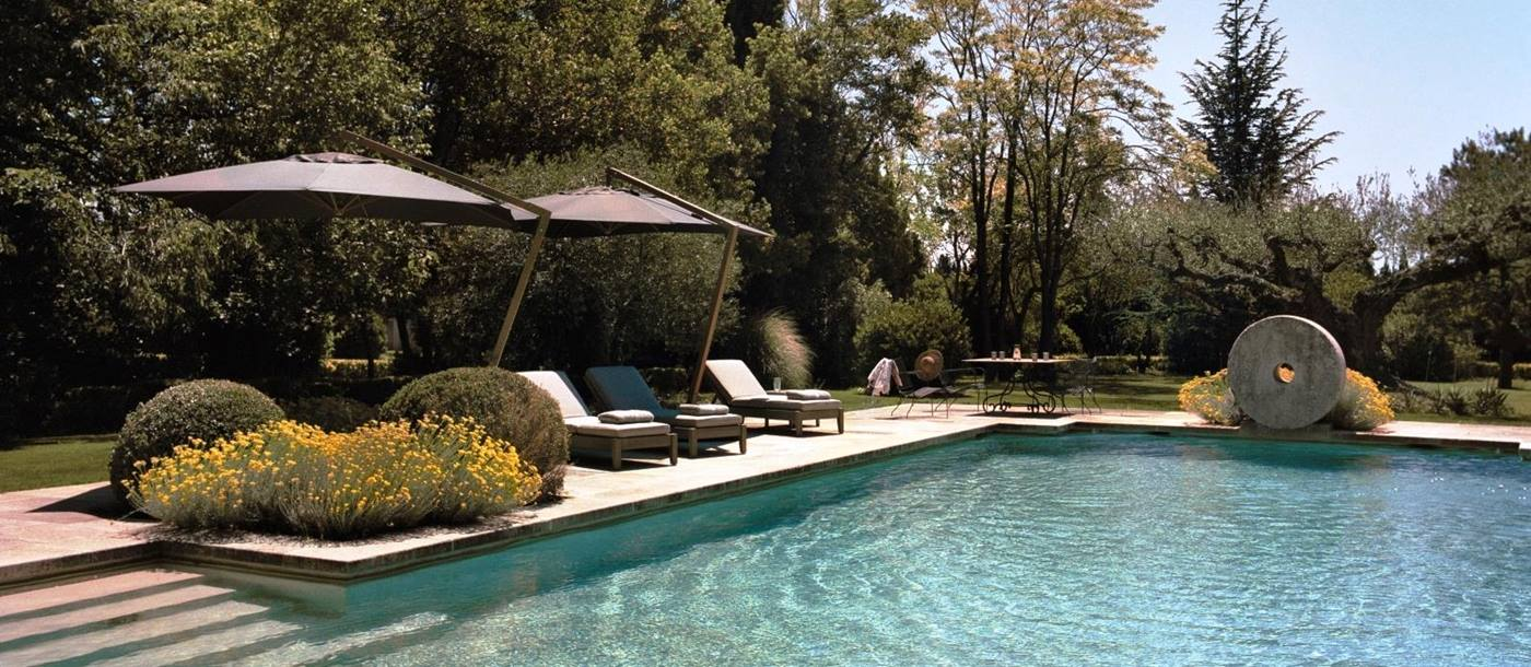 swimming pool set in the garden with three sun loungers under large brown sun canopies at Le Mas de Liliana, a luxury villa in Provence