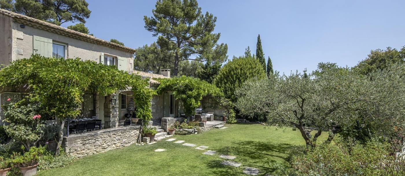 Façade and garden with trees, plants and flowers at Mas Cecile in Provence, France