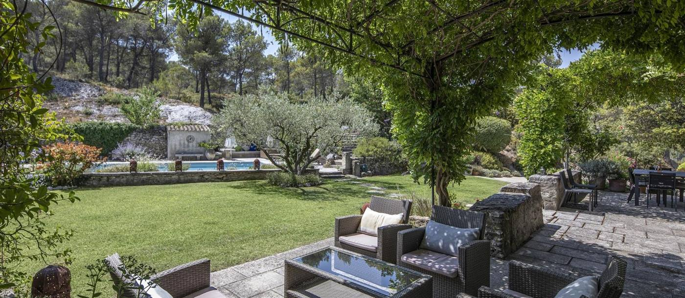 Outdoor lounge area with vines, sofas, armchairs, coffee table and view of pool and garden at Mas Cecile in Provence, France
