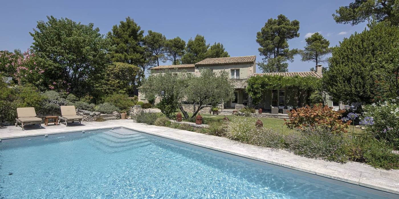 Pool, sun loungers, villa and garden with plants, flowers and trees at Mas Cecile in Provence, France