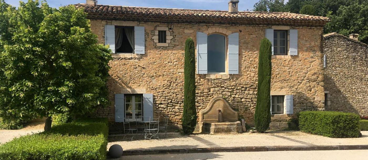 Facade, trees, hedges, boules court and dining table at Mas des Cerisiers in Provence, France
