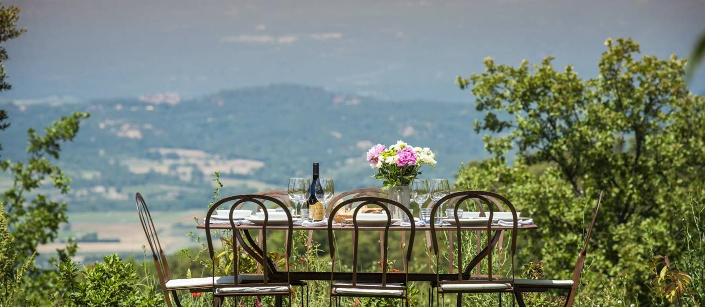 Outdoor dining area with set table, chairs, flowers and countryside view at Mas du Buis in Provence, France