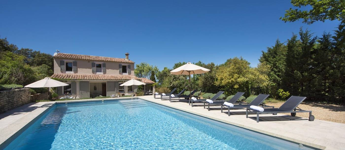 Pool and pool area with sun loungers, towels and umbrellas at Mas du Buis in Provence, France