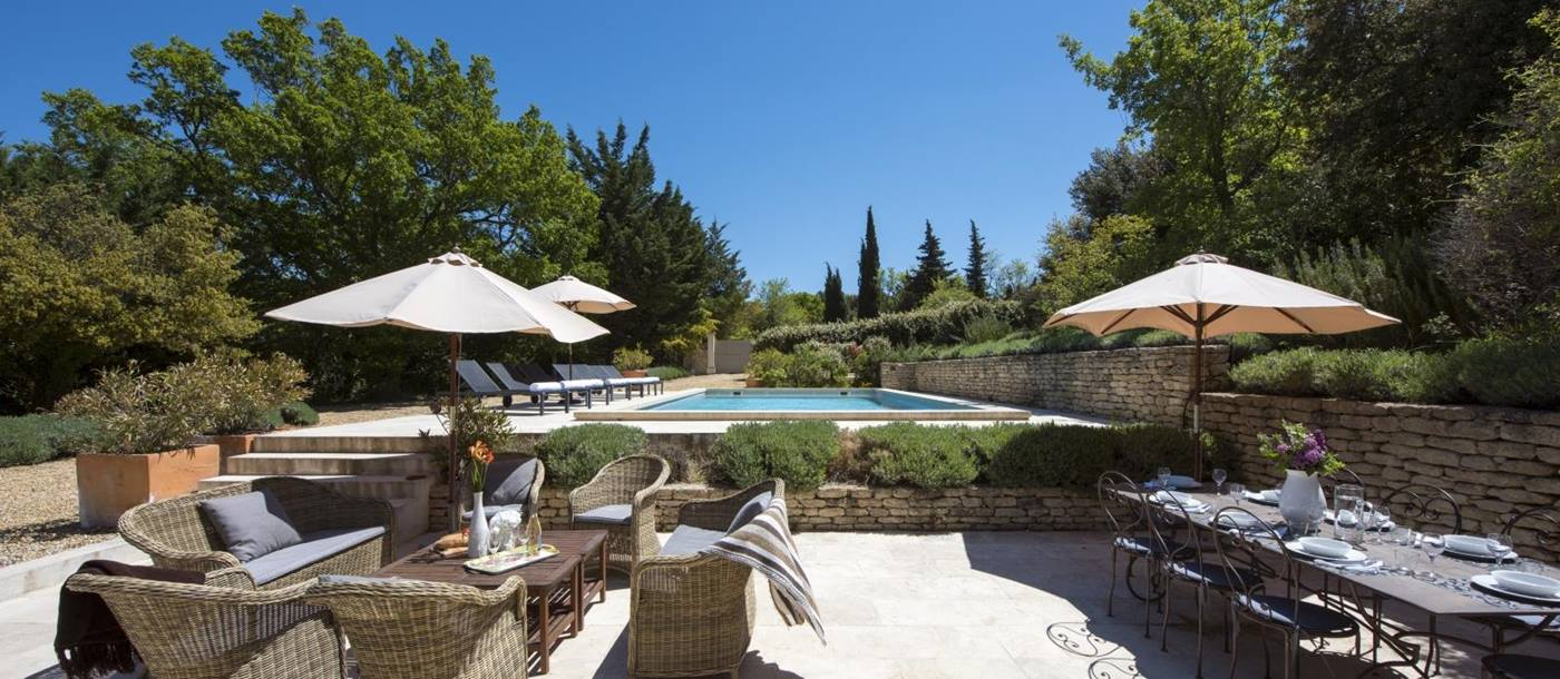 Terrace next to pool with comfy chairs, coffee table, umbrellas & dining table & chairs at Mas du Buis in Provence, France