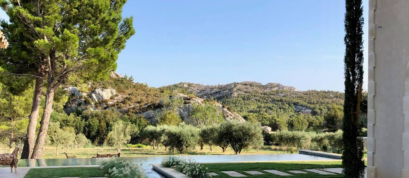 Garden with stepping stones, pool, sheep statues, plants, trees and mountain view at Villa Athena in Provence, France