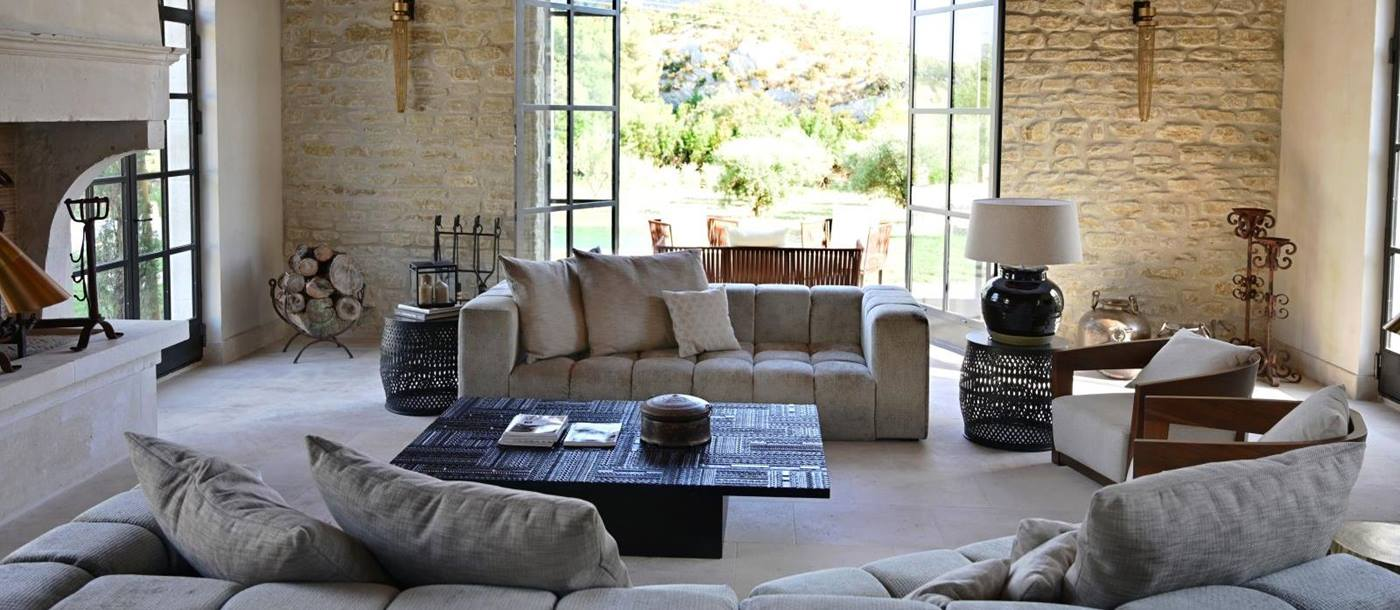 living area with two grey coloured sofas, coffee table and large open windows onto the garden at Villa Athena in Provence