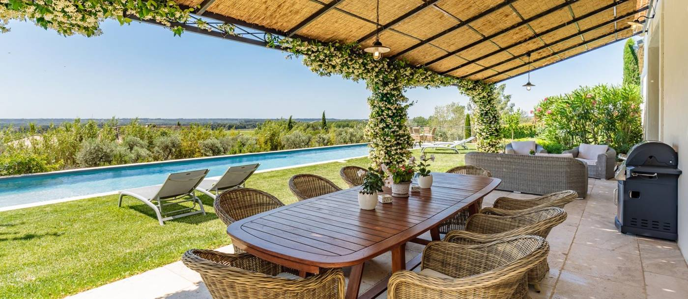 Terrace with dining table, comfy chairs, sofas, BBQ and view of pool and countryside at Villa Isa in Provence, France