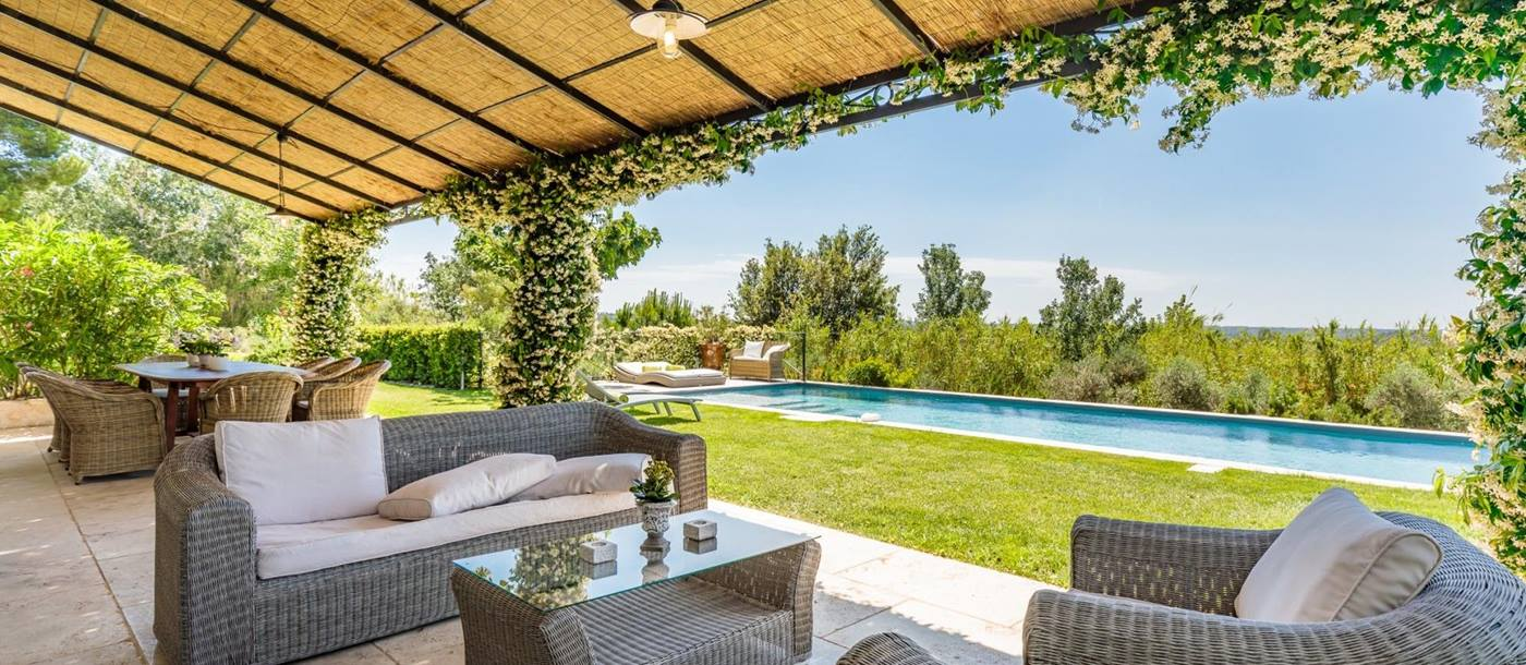 Covered terrace by pool with sofas, coffee table, dining table, chairs and jasmine at Villa Isa in Provence, France