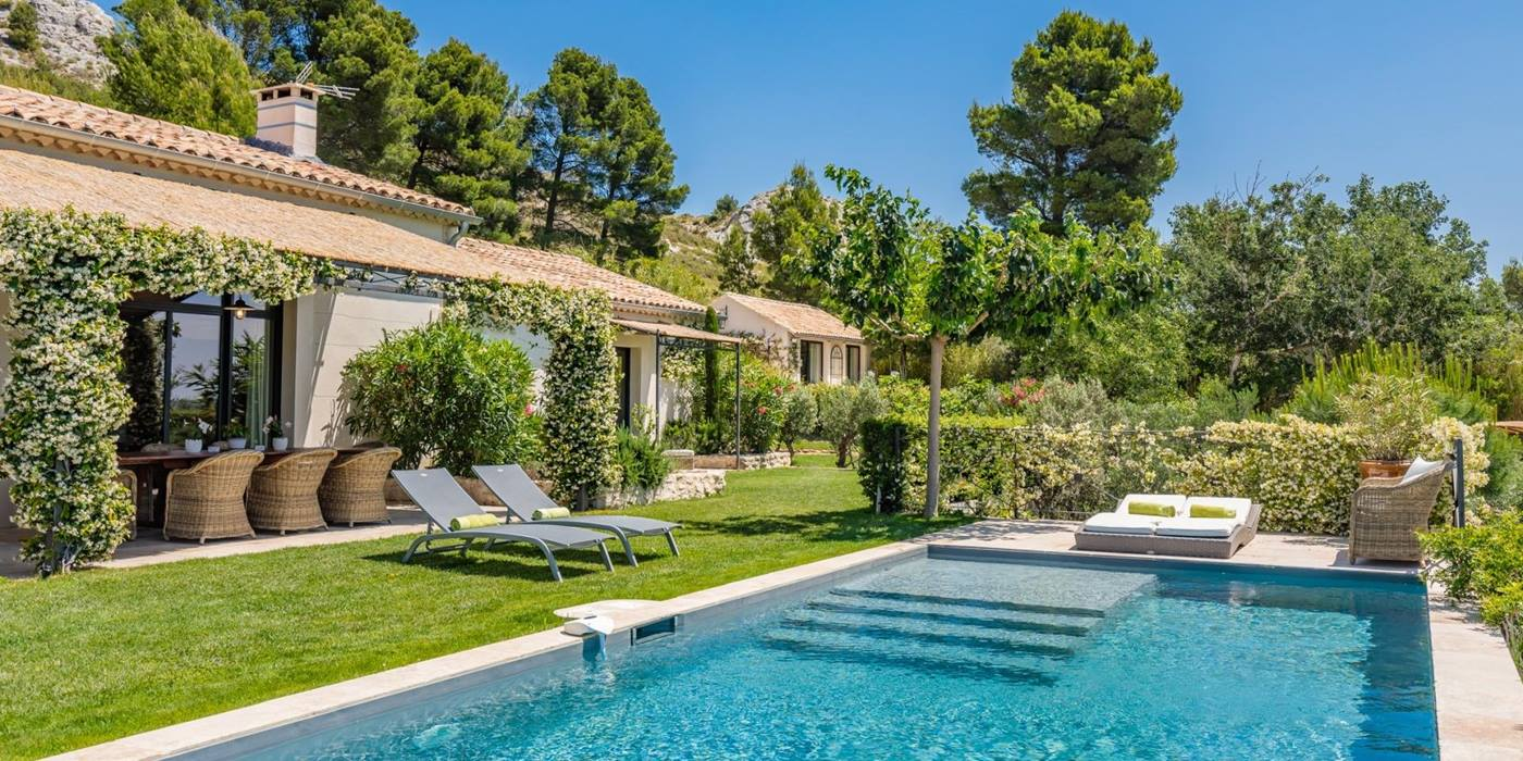 Pool and pool area with sun loungers and view of Les Alpilles at Villa Isa in Provence, France