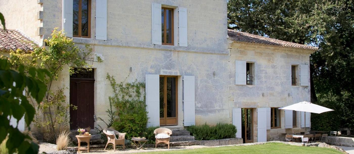 Façade and front garden with plants, coffee tables and comfy chairs at La Colline Bleue in South West France