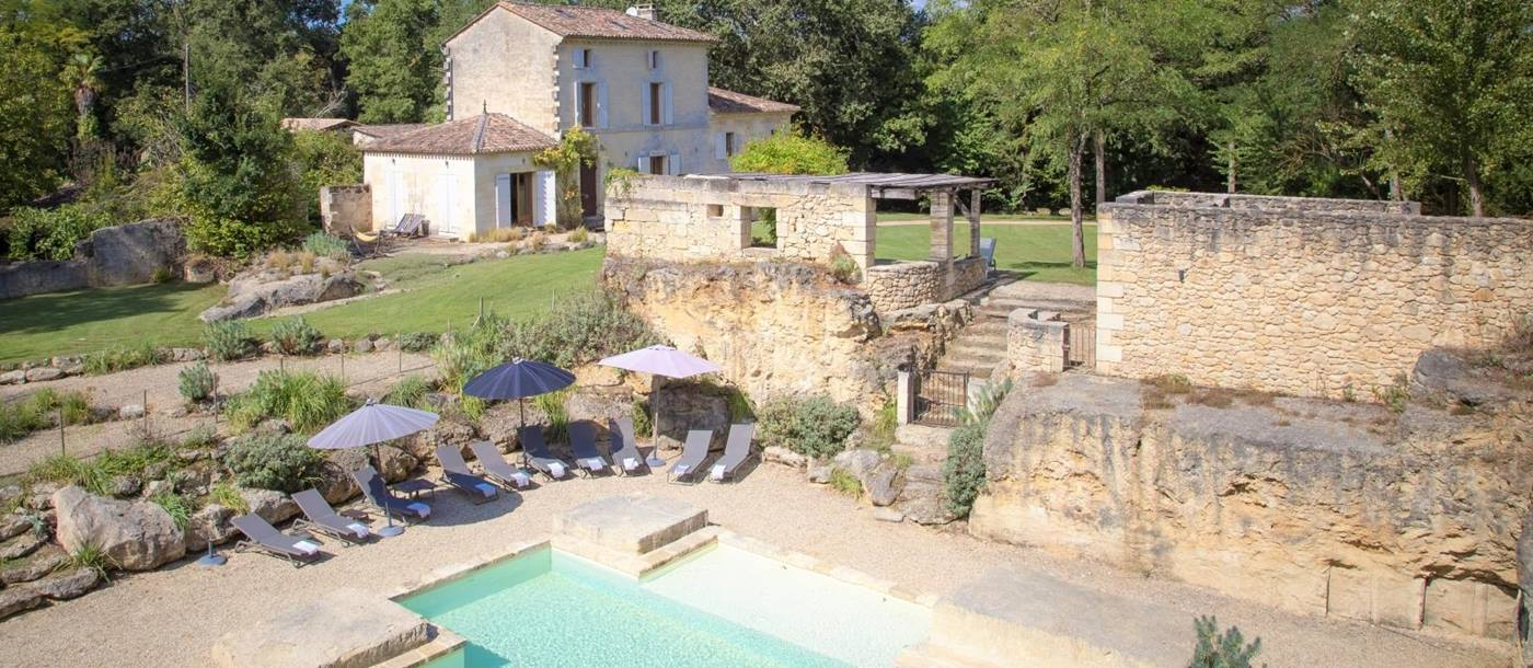 View of villa, gardens, pool and pool area at La Colline Bleue in South West France