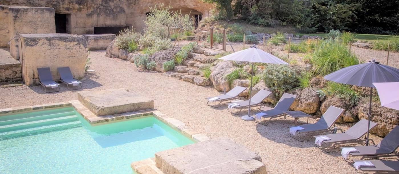 Pool and gated pool area with sun loungers, umbrellas and plants at La Colline Bleue in South West France