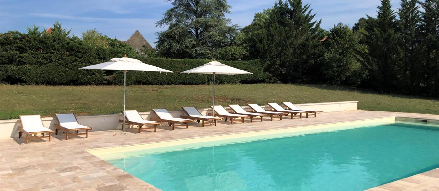 Pool and pool area with sun loungers and umbrellas at Maison de Cales in South West France