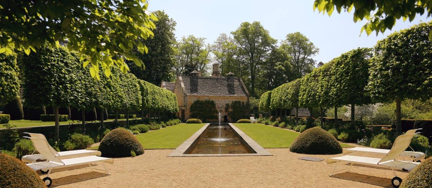 Garden with flowers, sun loungers, hedges, lawn, pond and trees at The Estate at Temple Guiting in the Cotswolds, England