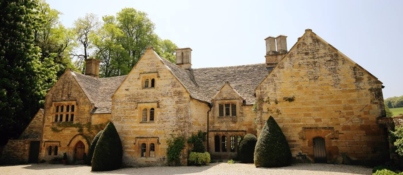 Cotswold stone front of house with hedges and plants at Temple Guiting Manor in the Cotswolds, England
