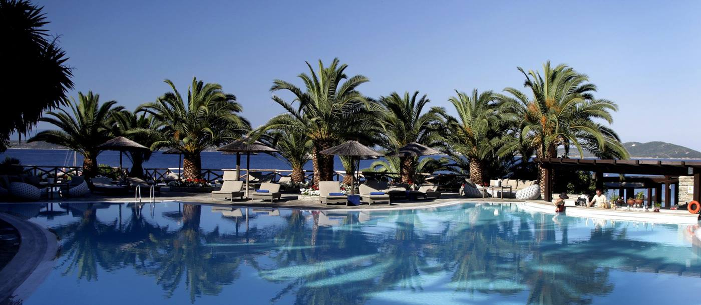 The swimming pool with palm trees at Eagles Palace, Greece