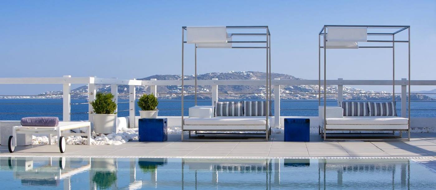 Sunloungers between sea and poolside of Grace Mykonos, Greece