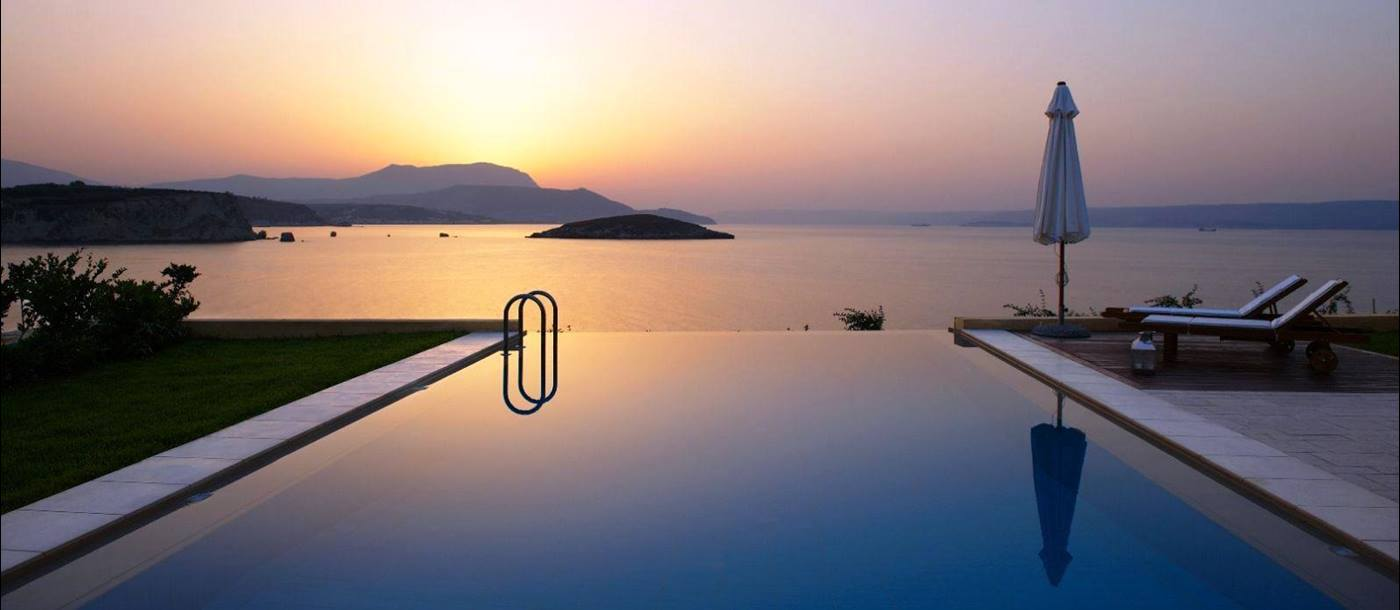 Swimming pool overlooking sea and mountains in the distance at sunset at villa anemos in crete